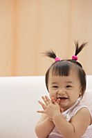 Baby Girl clapping hands and laughing, looking at camera - Asia Images Group