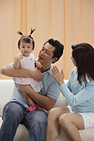 Mother and Father with baby girl, sitting on couch, happy - Asia Images Group