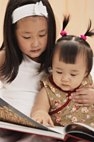 Baby girl with older sister, reading book together - Asia Images Group