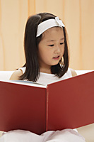 young female child reading book, sitting on couch - Asia Images Group