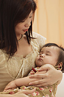 mother holding baby girl in arms, baby sleeping, mother looking at baby - Asia Images Group