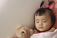 baby girl sleeping with teddy bear under blanket - Asia Images Group