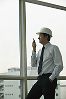man wearing hard hat, talking into walkie talkie and looking out window - Asia Images Group