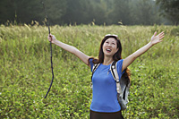 Woman hiking in nature, raising arms to the sky and smiling - Asia Images Group