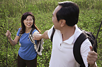 Man and woman hiking outdoors, nature, holding hands, looking at each other - Asia Images Group