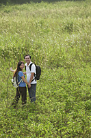 Man and woman hiking in nature, outdoors, looking at camera - Asia Images Group