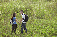 Man and woman hiking through tall grass, nature, outdoors - Asia Images Group