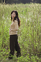 Woman standing in tall grass, looking over shoulder at camera - Asia Images Group