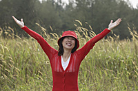 Woman standing in tall grass, arms raised to sky, happy, smiling - Asia Images Group