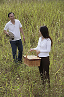 Man and woman walking outdoors, carrying picnic basket and blanket - Asia Images Group