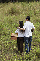 Man and woman walking in nature, holding picnic basket, back to camera - Asia Images Group
