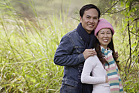 Man and woman wearing hat and scarves, standing outdoors in nature, smiling at camera - Asia Images Group