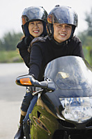 Man and woman riding motorcycle, wearing helmets, looking at camera - Asia Images Group