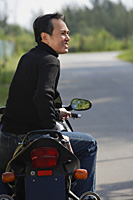 Man sitting on Motorcycle, looking away - Asia Images Group