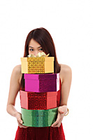 Young woman holding four presents, face hiding behind pile of presents - Asia Images Group