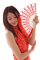 Young woman wearing cheongsam and holding traditional Chinese fan - Asia Images Group