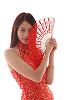 Young woman wearing cheongsam and holding Chinese fan - Asia Images Group
