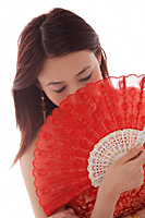 Young woman holding fan in front of face - Asia Images Group