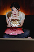 Young woman eating popcorn and watching TV - Asia Images Group