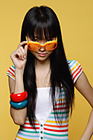 Young woman peering over sunglasses - Asia Images Group