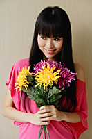 Young woman holding bouquet of flowers - Asia Images Group