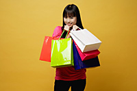 Young woman holding shopping bags close to herself, smiling - Asia Images Group