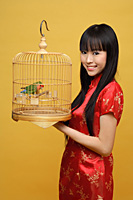 Young woman holding lovebird in bird cage, smiling - Asia Images Group