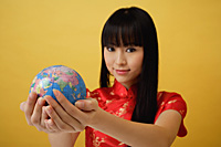 Young woman wearing red cheongsam and holding globe in the palm of her hands - Asia Images Group