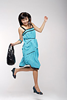 Young woman wearing blue dress, holding purse and jumping - Asia Images Group
