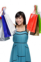 Young woman wearing blue dress and holding shopping bags up in air - Asia Images Group