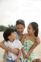 Mother, daughter and son sitting on beach together - Asia Images Group