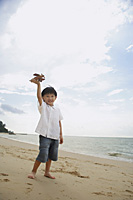 young boy on beach flying wooden airplane - Asia Images Group