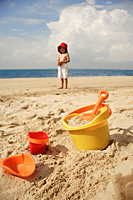 Young boy on beach, beach bucket and toys in foreground - Asia Images Group
