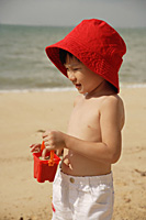 Young boy on beach, wearing red hat and carrying red beach bucket - Asia Images Group