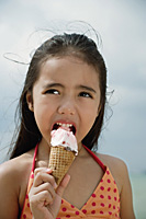 Young girl on beach eating an ice cream cone - Asia Images Group