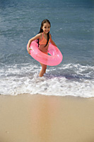 Young girl on beach carrying pink float around waist - Asia Images Group