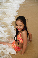 Young girl sitting on beach with waves crashing over her, smiling - Asia Images Group
