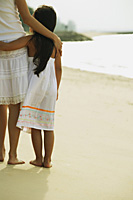 Mother and daughter standing on beach, arms around each other, rear view - Asia Images Group