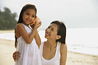 Mother and daughter on beach, daughter with conk shell to ear listening to ocean - Asia Images Group