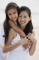 Daughter behind mother with arms over shoulders, smiling, hugging, on the beach - Asia Images Group