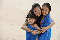 Mother, son and daughter on beach, kids wrapped in blue towel, mother hugging children - Asia Images Group