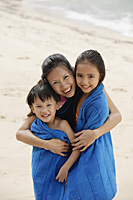 Mother on beach with son and daughter, mother hugging children and wrapping them in blue towel - Asia Images Group