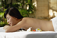 Young woman laying on massage table, eyes closed, spa - Asia Images Group