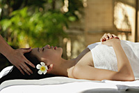 Young woman receiving massage while laying on massage table, spa - Asia Images Group