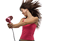 Young woman blow drying hair with hair flying - Asia Images Group