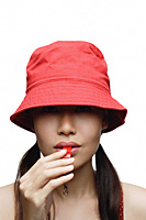 Girl in red blowing whistle, head shot - Asia Images Group