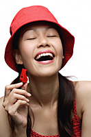 Young woman wearing red hat and holding whistle, laughing - Asia Images Group