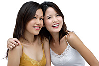 Two young women, arms around each other, smiling - Asia Images Group