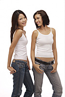 Two young women standing together smiling - Asia Images Group