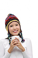 Young woman wearing winter hat, holding mug of hot chocolate - Asia Images Group